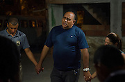 Preacher Célio Ricardo, in the center, leads a pray in Amor de Deus Recovery Center, Del Castilho, Rio de Janeiro. Before each night of social action and evangelism, the evangelism team get together with the preacher to pray.
