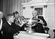 Replica Of Sam Maguire Cup Assayed.  (R85)..1988..18.08.1988..08.18.1988..18th August 1988..The Sam Maguire Cup which was first won by 1928 All Ireland Champions, Kildare is being replaced by a replica for the 1988 final. The original cup was wrought by Hopkins and Hopkins of Dublin to the design of the Ardagh Chalice and is made of silver..The replica has been made by Kilkenny based silversmith Mr Desmond Byrne. the silver for the replica wa presented to the GAA by Mr Kieran Eustace, Managing Director, Johnson Matthey, Grafton Street, Dublin. The replica is hand crafted to match the eacct design and dimensions of the original. Today in Dublin Castle the new 'Sam Maguire' was stamped with the Millennium Stamp by the Assay Master, Dublin Castle...Image shows the new 'Sam Maguire' being examined by  Mr Kieran Eustace,Managing Director, Johnson Matthey Ltd,Mr Desmond Byrne, Silversmith,Kilkenny who made the replica, Mr Lorcan O'Rourke,Development manager, GAA,  and Mr Ronnie LeBas,retired, Assay Master of the Goldsmiths Co,Dublin Castle after the stamping of the cup with the Millennium stamp.