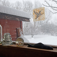 Souvenirs line the sill of a window looking out at a snowstorm near Bozeman, Montana.