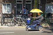Een oudere moslim kijkt terwijl hij op een scootmobiel rijdt tijdens de ramadan naar etende mensen in de Kanaalstraat in Utrecht. Om zich te beschermen tegen de zon heeft hij een paraplu.<br /> <br /> A moslim on a scooter is watching how people are eating during ramadan. To protect himself against the sun he is using an umbrella.