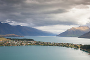 Landscape with view of town on shore and mountains across Lake Wakatipu, near Queenstown, South Island, New Zealand