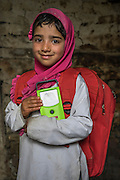 Muskaan, 6, holds a small solar lamp from the education kit in her collapsed house in Purnishadashah village, Jammu and Kashmir, India, on 24th March 2015. Muskaan's house was destroyed in the floods forcing her family to move in with relatives. Save the Children supported the family with kitchen items, hygiene kits, food baskets, blankets, a solar powered lamp and education kits for the children. Photo by Suzanne Lee for Save the Children