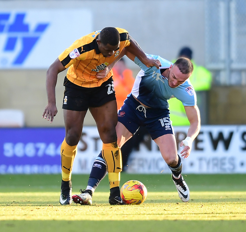 Cambridge United's Uche Ikpeazu vies for possession with Blackpool's Tom Aldred<br /> <br /> Photographer Chris Vaughan/CameraSport<br /> <br /> The EFL Sky Bet League Two - Cambridge United v Blackpool - Saturday 14th January 2017 - The Cambs Glass Stadium - Cambridge<br /> <br /> World Copyright © 2017 CameraSport. All rights reserved. 43 Linden Ave. Countesthorpe. Leicester. England. LE8 5PG - Tel: +44 (0) 116 277 4147 - admin@camerasport.com - www.camerasport.com