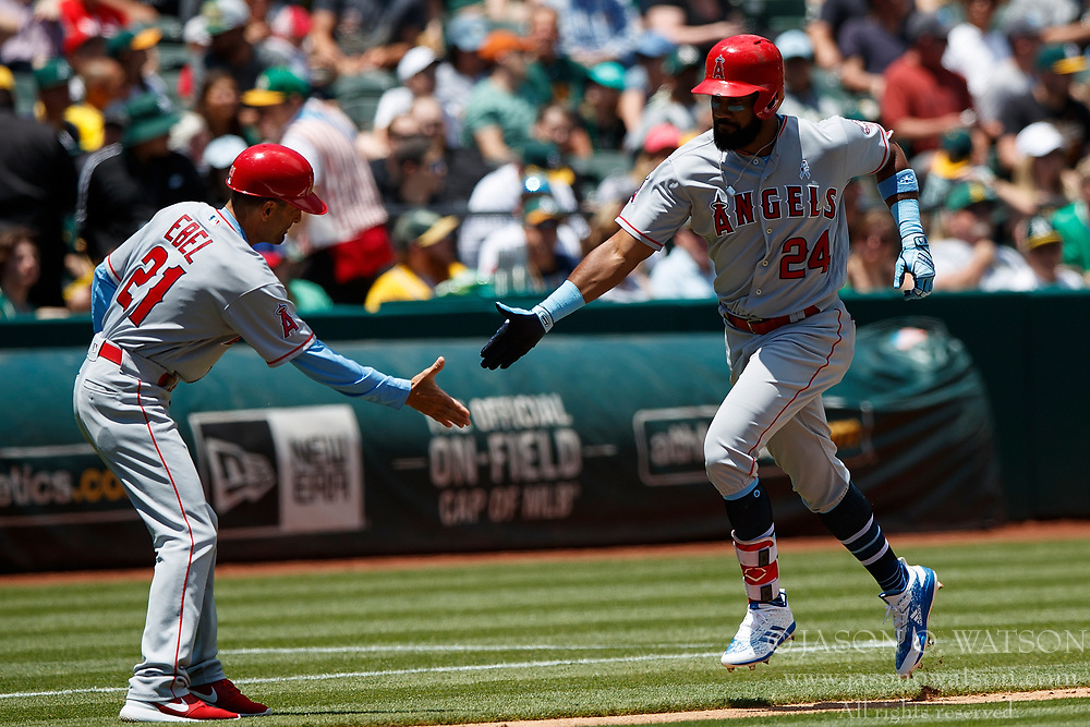 OAKLAND, CA - JUNE 17: Chris Young #24 of the Los Angeles Angels of Anaheim is congratulated by third base coach Dino Ebel #21 after hitting a home run against the Oakland Athletics during the third inning at the Oakland Coliseum on June 17, 2018 in Oakland, California. The Oakland Athletics defeated the Los Angeles Angels of Anaheim 6-5 in 11 innings. (Photo by Jason O. Watson/Getty Images) *** Local Caption *** Chris Young; Dino Ebel