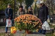 A family remembers a deceased loved one at the Rakowicki Cemetery in Krakow, Poland 2019.
