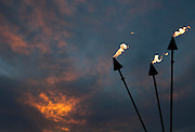 Fire flies from tiki torches with sunlit clouds at sunset on Waikiki Beach.