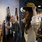 Abby Adesanya, right, tries on a hat with Elly Ayres at Two Old Hippies in downtown Nashville, Tennessee. Nathan Lambrecht/Journal Communications