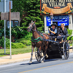 Intercourse, PA - June 12, 2016: Amish use a horse-pulled buggy for transportation on a village road in Lancaster County.
