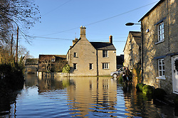 © Licensed to London News Pictures. Date 24 December 2013. Ascott Under Wychwood. Flooded houses and road at Ascott Under Wychwood.  Flooding images - River Evenlode in full flood.. Photo credit : MarkHemsworth/LNP