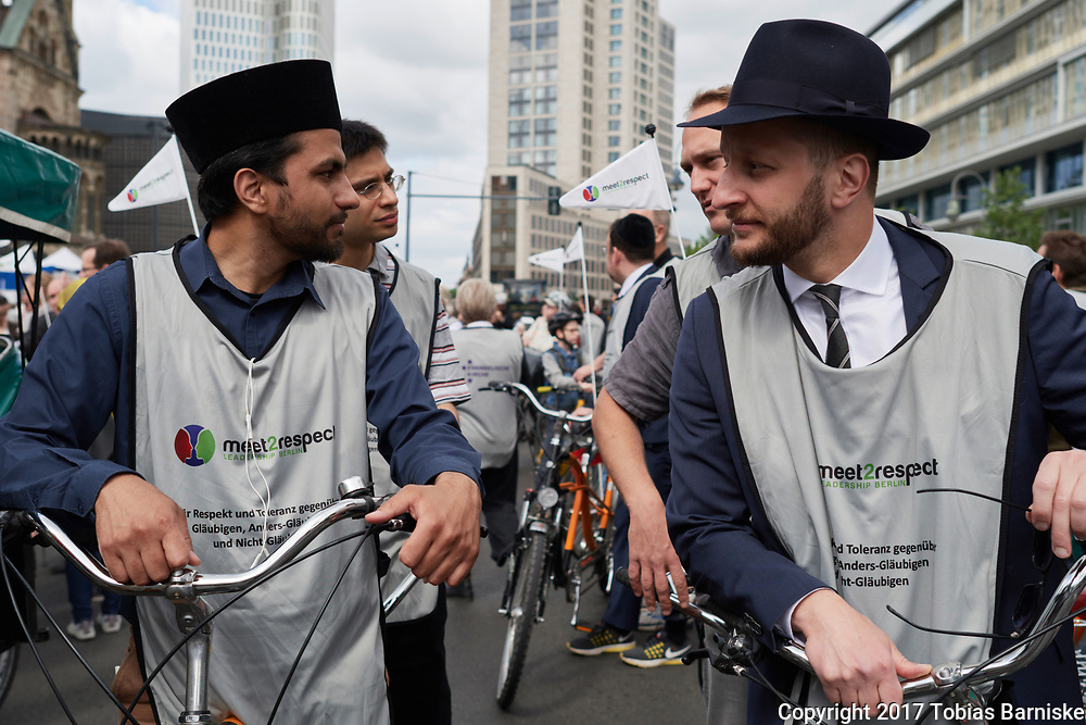 Members of different faiths and religions - priests, rabbis and imams - doing a bicycle tour together; promoting the idea of respect and tolerance towards other religious and non-religious people.