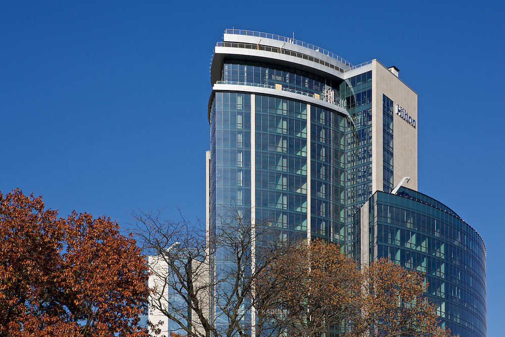 Exterior view of Hilton hotel in Kyiv, Ukraine. Daylight, sunny autumn day, view from the botanic garden.