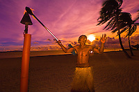 Fijian man lighting tiki torches on beach at sunset, Westin Resort and Spa, Denarau Island, Fiji Islands
