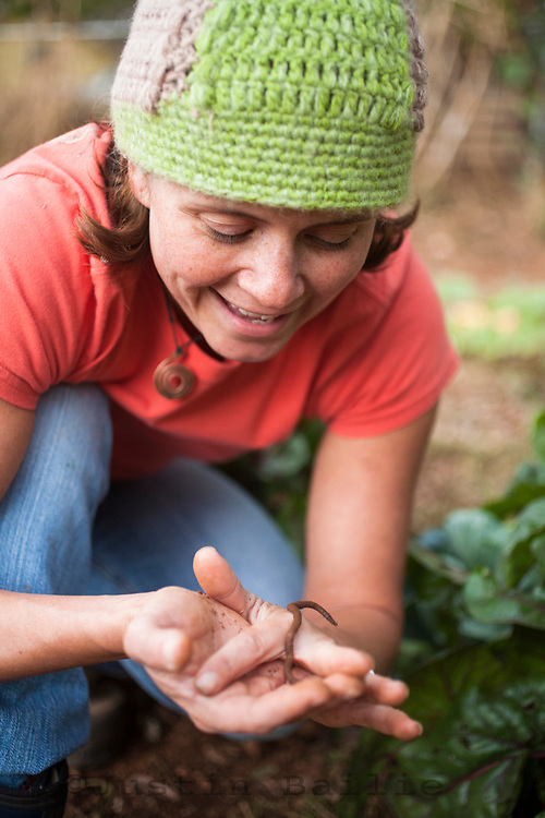 Portrait of young woman looking at earthworm while working on farm.