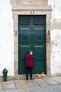 Old woman returns home after walking her chihuahua dog  in historic town of Guimaraes in Northern Portugal