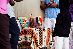 Akinyemi Blake and his son Obayemi light six of the seven Mishumaa Saba (seven candles) in celebration of the sixth day and principle of Kwanzaa, Kuumba which means Creativity.