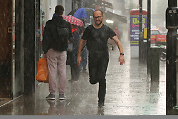 © Licensed to London News Pictures. 17/05/2021. London, UK. A man is caught in the heavy rain in north London. More rain is forecast for the South East of England this week. Photo credit: Dinendra Haria/LNP