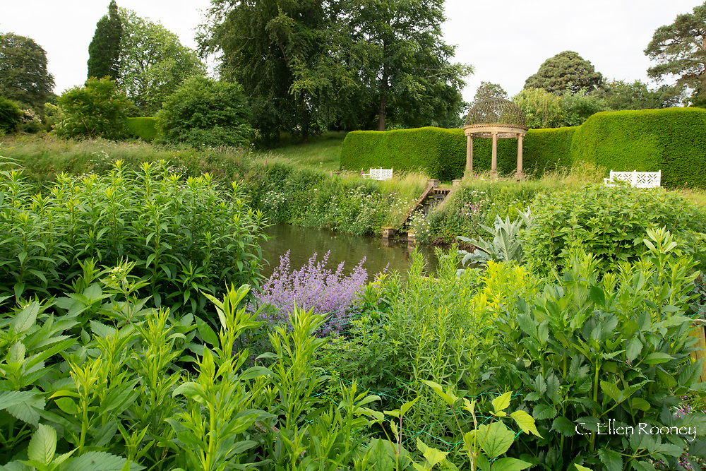An Ionic temple and lush planting around the long pond at Forde Abbey, Chard, Dorset, UK