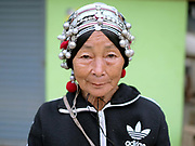 An Akha woman wearing her traditional headdress at Meung Long market, Luang Namtha province, Lao PDR. Made from hand forged silver, coins, handwoven cotton, market bought cotton, plastic beads, bamboo, cowrie shells and woollen tassels women would traditionally wear their headdress even while bathing, sleeping and working in the fields.