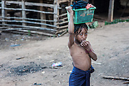 A village girl walks back with her laundry after bathing in her village, northern Laos