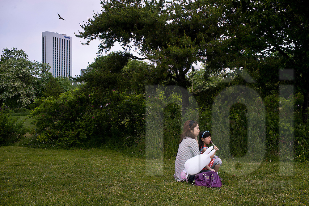 A young Japanese girl sits on her mother's lap in a grassy city park, Japan, Asia
