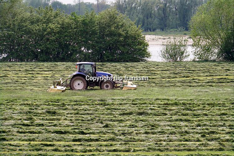 Nederland, Loenen, 23-4-2019In de uiterwaarden van de rivier de Waal maakt een boer gebruik van het mooie weer om gras te maaien. Daarna wordt het tot balen gepakt en als wintervoer aan het vee, de koeien, gevoerd. Foto: Flip Franssen
