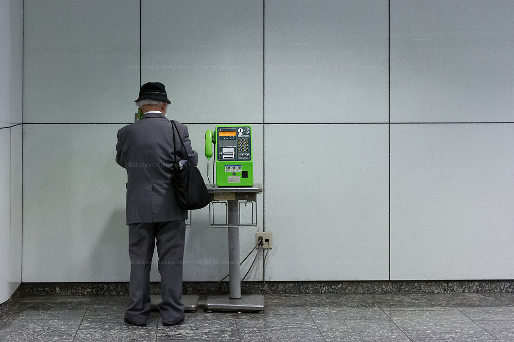 An older Japanese man uses a payphone in Shinjuku Station, Shinjuku, Tokyo, Japan. Wednesday April 28th 2021. There are currently about 260,000 public payphones in Japan, There are currently around 151,000  pay-phones in Japan. Due to increased cell phone usage the government is looking to reduce that number by up to 75 percent.