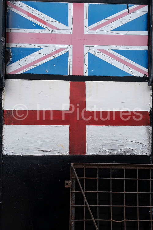 Disintegrating and cracking painted St Georges Cross and Union Jack flags aka Union flag on 13th April 2021 in London, United Kingdom. In heraldry, Saint Georges Cross, also called the Cross of Saint George, is a red cross on a white background. These decaying flags seem like a metaphor of the potential breaking up of the UK.