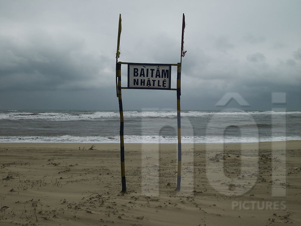 Le Nhat beach by a stormy day. There's a sign in vietnamese to inform the name of the beach. It's drived in sand Quang Binh, Viet Nam.