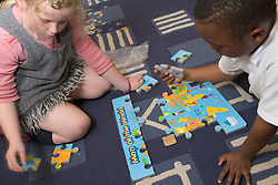 Primary school pupil doing a jigsaw puzzle during an After School Club,