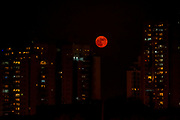 Full orange moon rises over an urban cityscape