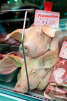 whole pig heads for sale, as promotion, in a Paris butcher
