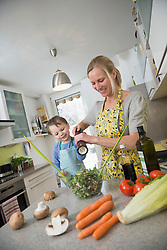 Boy preparing salad with his mother, smiling