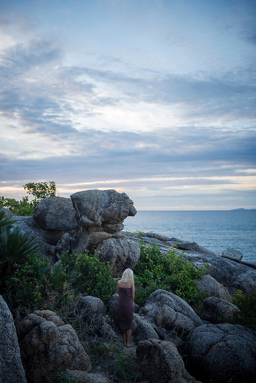A woman wearing a sarong stands on the rocky coastline of Ko Phangan, Thailand. (October 2017)