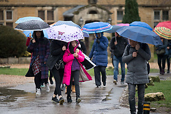 © Licensed to London News Pictures. 08/02/2019. Bourton-on-the-Water, Gloucestershire, UK. Tourists arrive holding umbrellas during a rain shower on a wet and windy day in Bourton-on-the-Water in Gloucestershire, UK. Photo credit: LNP