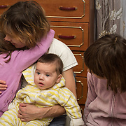 """CAPTION: With four young chldren, Oksana really has her hands full. """"Without Partnership For Every Child's short break service"""", she says, """"my children would have gone into a children's home and I would never have got them out"""". NAME MUST BE CHANGED. LOCATION: St Petersburg, Russia. INDIVIDUAL(S) PHOTOGRAPHED: Elena Orlova (girl on left), Oksana Orlova (mother), Kseniya Orlova (baby) and Diana Orlova (girl on right)."""