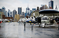 Looking toward NYC from the flight deck of the carrier Intrepid showing a variety of military aircraft. The carrier is now the feature of the Intrepid Sea, Air & Space Museum located on the Hudson River.