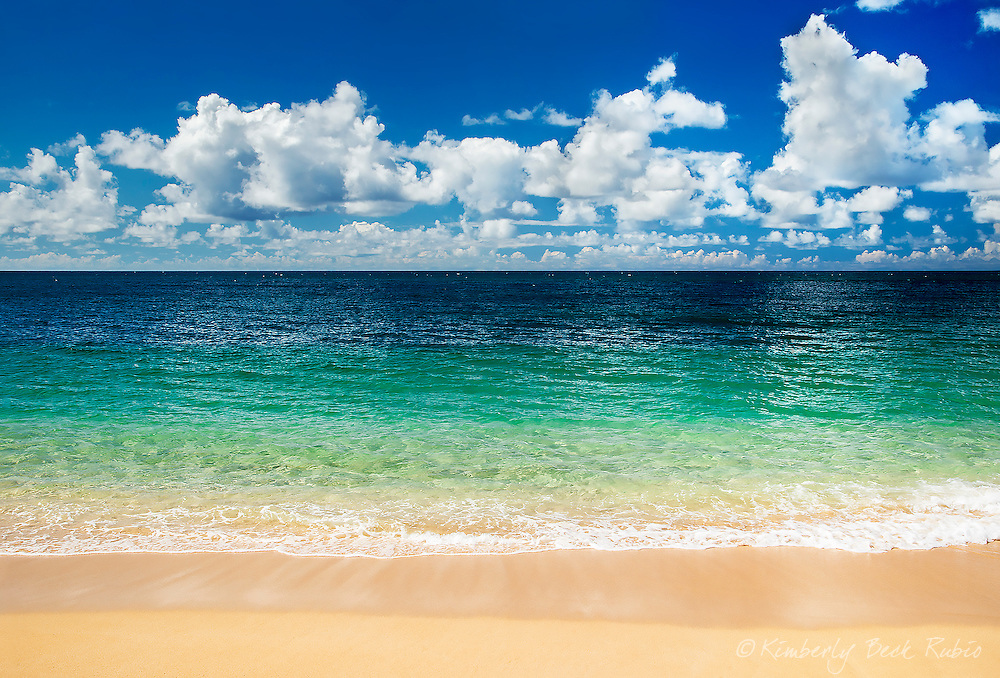 Waveless summer beach day at Sunset Beach looking toward Banzai Pipeline on the North Shore of Oahu, Hawaii.