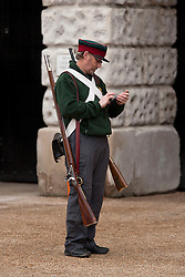 © Licensed to London News Pictures. 12/06/2012. LONDON, UK. A reenactor of the 'Moscow Militia' uses his mobile phone during a dress rehearsal ahead of the annual Beating Retreat ceremony on Horse Guard's Parade today (12/06/12). Photo credit: Matt Cetti-Roberts/LNP