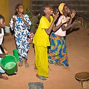 The night before Tamkharit (Islamic New Year), Koumbadiouma's children dance for grain handouts at each of the village's compounds. The grain is used to make a tasty meal the next day. Kolda, Senegal.