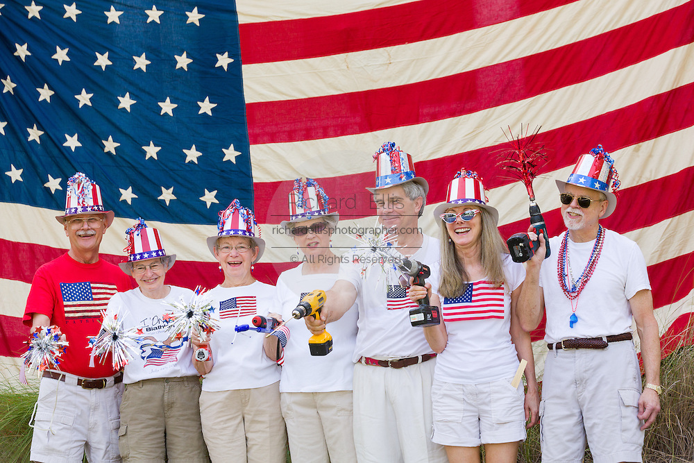 """Members of the """"Precision Drill Team"""" pose in front of an American flag during the I'On neighborhood Independence Day parade July 4, 2015 in Mt Pleasant, South Carolina. The team parades using battery operated drills as their novelty."""