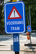 "Blue road warning sign ""Voorrang Tram"" at a pedestrian street crossing in Ghent, Belgium."