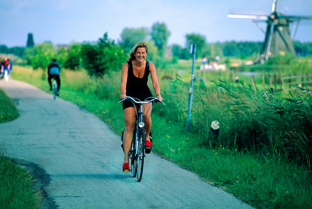 Dutch woman riding a bike along a path near the windmills at Kinderdijk, The Netherlands