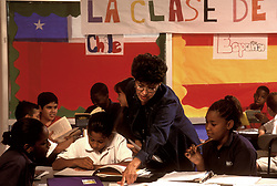 Stock photo of a teacher helping young students with their Spanish work