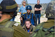"""Every Friday afternoon since 2005, residents of the Palestinian village of Bil'in, joined by Israeli and international activists, have protested the Israeli-built separation barrier that separates the village from approximately 60 percent of its agricultural land. A documentary about the protest, 5 Broken Cameras, was nominated for an Academy Award in 2013.<br /> <br /> It was at this protest in 2006 that I met Olga Ginzbourg, a 22-year-old student majoring in economics and sociology at Tel Aviv University. During the two hours in which demonstrators would attempt to pull back razor wire at the barrier and soldiers would respond with stun grenades and batons, she stood out. In part it was her light brown hair in a sea of dark hair and helmets. But what most drew me in was her sincerity, both as she interacted with the villagers and as she engaged the soldiers.<br /> <br /> In the spring of 2006, Olga studied in Spain and met people who challenged her views of the conflict. They talked about what happened in 1948 and what was happening even now in the Occupied Territories. While not convinced of their perspective, she returned to Israel mulling over the narrative they had presented her. When later in the year she saw a poster in Tel Aviv announcing a large demonstration to be held in a troubled Palestinian village called Bil'in, she decided it was time to go see things for herself. And so on October 27, 2006, for the first time in her life, she visited the occupied West Bank. The experience transformed her.<br /> <br /> When asked about her own parents, particularly what they thought of their only daughter's new interest in the lives of Palestinians, Olga said they were terrified. """"You could lose your life for nothing,"""" her dad insisted. But Olga countered, """"How can I not do something when I am privileged, when Palestine is only a few kilometers from my house?""""<br /> <br /> __________<br /> <br /> <br /> Now in their 11th year, the protests in Bil'in continue."""