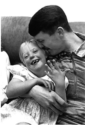 Father sitting on sofa in living room with arm around young daughter with Downs Syndrome,