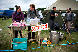© London News Pictures. 17/08/2013. Balcombe, UK. Campaigners wash dishes at a camp site organised by campaign group No Dash For Cash in Balcombe, West Sussex which has been earmarked for fracking. Cuadrilla has temporarily ceased drilling at the site under advice from the police after campaign group No Dash For Gas threatened a weekend of civil disobedience. Photo credit: Ben Cawthra/LNP