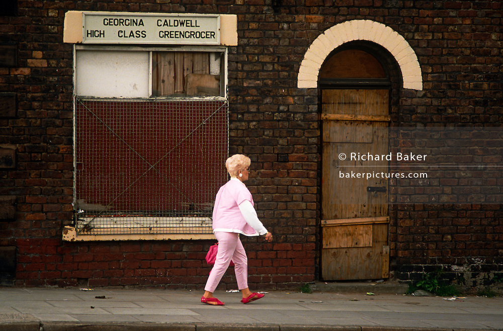 A middle-aged woman walks along a gloomy street in Toxteth, Liverpool, England. Passing a boarded-up greengrocer that probably once served the local community, the lady strides past its sealed window and the name of its past owner, obviously proud of her business' quality in an otherwise run-down area. Toxteth saw serious rioting in 1981 and the legacy of social-deprivation ever since meant a breakdown of law and order.  Used as the epitome of poor inner-city Britain, it is located to the south of the city and is synonymous with social issues, degradation and poverty with some of the most underprivileged families in the UK. Recently many streets in the worst areas have been demolished including a threat to Beatle Ringo Starr's childhood home.