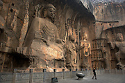 A chinese girl is dwarfed by the buddha statues carved into the walls of the Longmen Grottoes.<br /> <br /> The Longmen Caves are one of the finest examples of Chinese Buddhist art. Tens of thousands of statues of Buddha and his disciples,located 12 kilometres south of Luòyáng in Hénán province, are housed in caves.Sadly the vast majority of them have been ruined by thieves taking the heads off to sell.The images, many once painted, were carved into caves excavated from the limestone cliffs of the Xiangshan and Longmenshan mountains, running east and west. The Yi River flows northward between them.