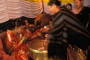 At a farewell party before a Newar wedding in the Kahmandu Valley, Nepal, friends and family offer the bride their congratualations and deposit gifts in a large brass bowl.
