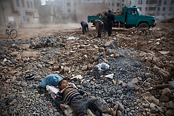 A child sleeps at demolition site in Old City, Xinjiang, China.